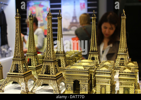 Tourist shop inside of the Arc de Triomphe - miniature Eiffel Towers and mini triumphal archs with people on the - Stock Photo