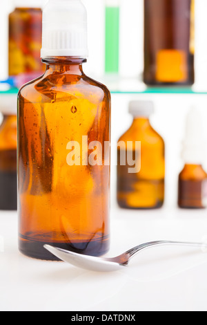 Bottle with flue mixture and spoon on foreground with two shelves with bottles and test tubes on background - Stock Photo