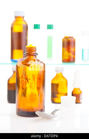 Spoon and cold mixture with different drugs in jars, bottle and test tubes standing on shelf with medicine - Stock Photo
