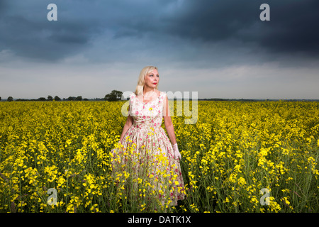 woman standing in field in open countryside with oilseed crop - Stock Photo