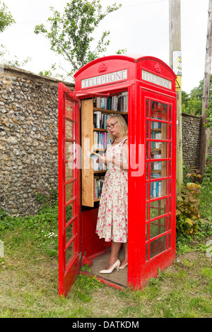 woman village library installed in disused red telephone box, Suffolk, UK - Stock Photo