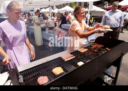 Amish girls selling hamburgers and hot dogs at farmers market - Washington, DC USA - Stock Photo