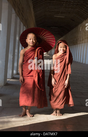 Two novice monks inside corridor of Shwezigon Pagoda, in Nyaung-U, Myanmar (Burma). - Stock Photo
