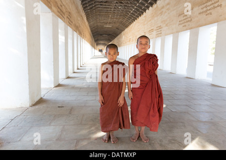 Two novice monks inside corridor of Shwezigon Pagoda in Nyaung-U, Myanmar (Burma). - Stock Photo