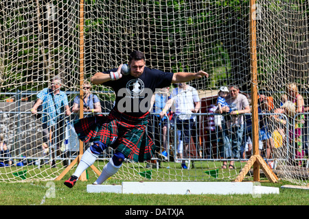 Competitor throwing the 16 pound ball in the traditional Scottish competition at the Highland Games, Balloch, near - Stock Photo