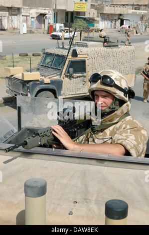 A British soldier of the Multinational Division South East is pictured with his SA80A2 assault rifle on a  Land - Stock Photo