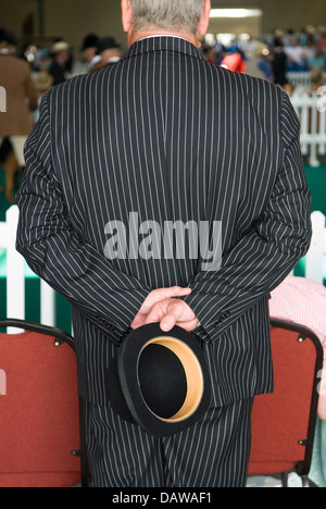 Man in pinstripe suit carrying a bowler hat  at the Peterborough Festival of Hunting England. 2010s UK HOMER SYKES - Stock Photo