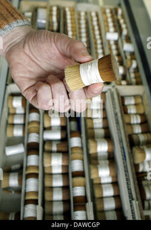 An employee holds a bundle of processed animal hair used for making brushes at the artist's brush factory Defet - Stock Photo