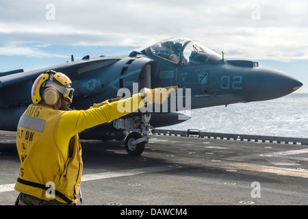 A US Navy Aviation Boatswains Mate signals to the pilot of an AV-8B Harrier fighter aircraft that he is cleared - Stock Photo