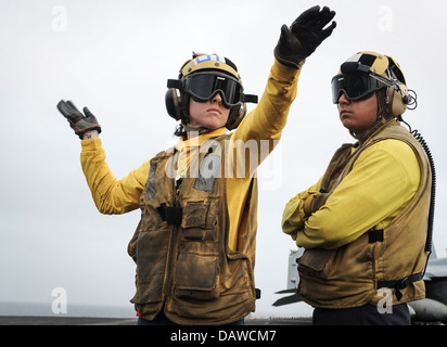 A US Navy Aviation Boatswain's Mate receives training on aircraft hand signals on the flight deck of the aircraft - Stock Photo