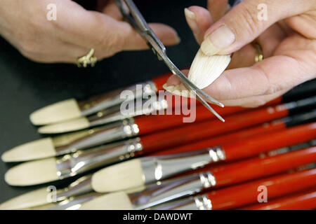 An employee cuts the tips of brushes with a pair of scissors at the artist's brush factory Defet Gmbh in Nuremberg, - Stock Photo