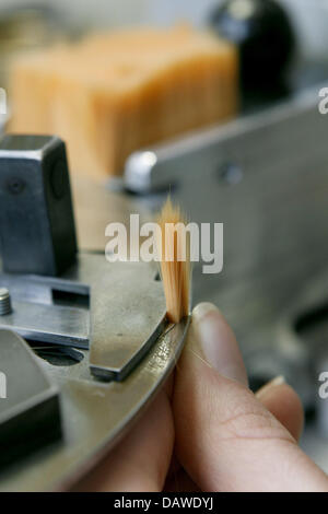 An employee assembles the parts of a brush at the artist's brush factory Defet Gmbh in Nuremberg, Germany, 27 February - Stock Photo