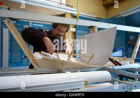 A visitor takes a look at a model of a Viking ship in the archeological workshop of the museum for Viking ships - Stock Photo