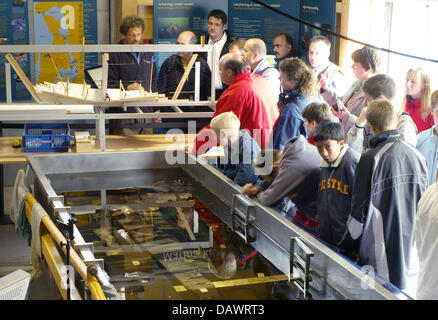 Visitors take a look at a model of a Viking ship in the archeological workshop of the museum for Viking ships in - Stock Photo