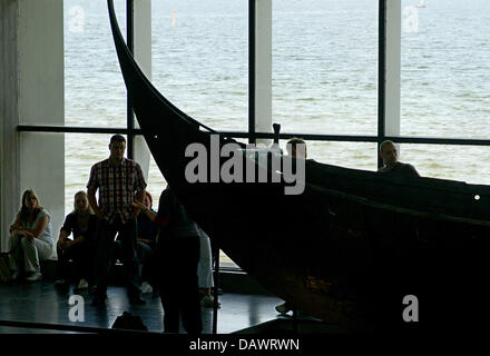 Visitors take a look at a reconstructed Viking ship of the 11th century, discoverd in the Roskilde fjord in 1962, - Stock Photo