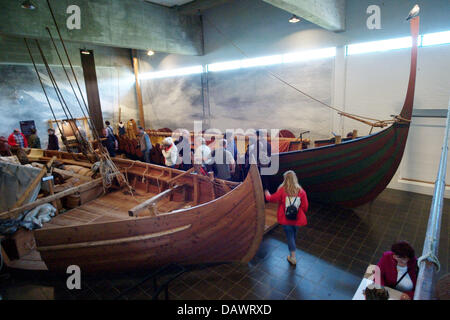Visitors take a look at reconstructed Viking ships from the 11th century, discoverd in the Roskilde fjord in 1962, - Stock Photo