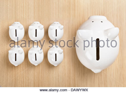 Piggy bank standing out from row - Stock Photo