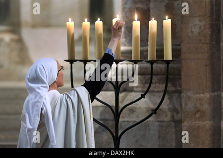 Candles are lit, candle stand in the roman catholic church Gross St. Martin in Cologne, Germany - Stock Photo