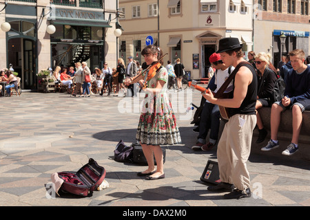 Buskers playing entertaining music in Amagertorv Square busy with people watching. Amager Torv, Copenhagen, Denmark - Stock Photo