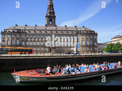 Tourists canal boat city sightseeing tour passing Christiansborg Palace on Slotsholmen Isle in Copenhagen, Zealand, Denmark