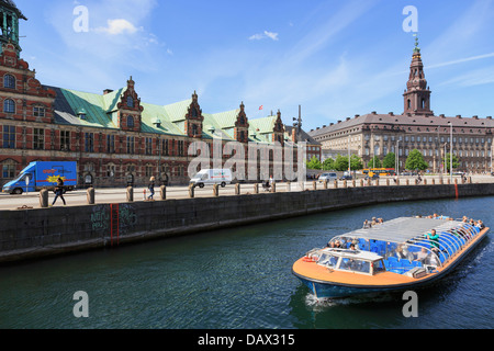 Tourists canal boat city sightseeing tour by Old Stock Exchange building Borsen and Christiansborg Palace in Copenhagen - Stock Photo