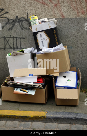 Cardboard boxes filled with paper on pavement in town waiting to be collected for recycling - Stock Photo