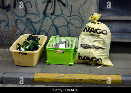 Plastic containers with glass bottles and garbage bag with household waste in front of house in city street - Stock Photo