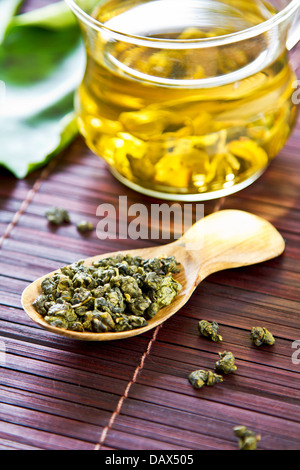 Oolong Tea leaf in a wooden spoon - Stock Photo