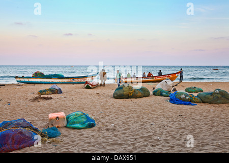 Fishermen sort out their fishing nets on the beach in Mahabalipuram, in the southern Indian state of Tamil Nadu. - Stock Photo