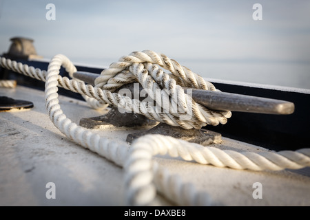 Close- up of boat cleat with a dirty white rope tied to it - Stock Photo
