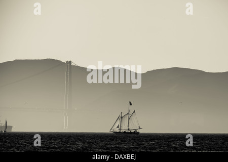 Monochrome image of two masted schooner approaches the Golden Gate Bridge shrouded in mist - Stock Photo