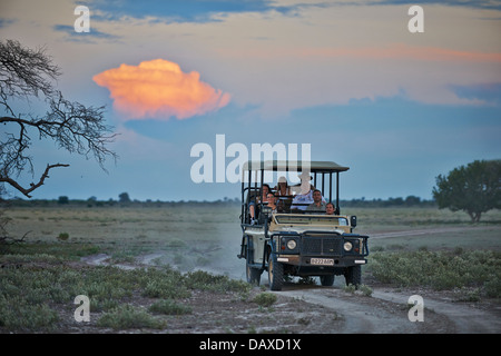4x4 safari car with tourists and guide during sunset in Central Kalahari Game Reserve, Botswana, Africa - Stock Photo