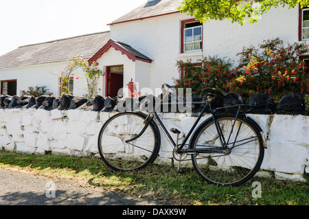 Old bicycle propped up against the wall of a whitewashed Irish farmhouse - Stock Photo
