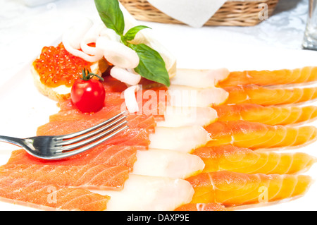 sandwiches with caviar and sliced fish on a white plate - Stock Photo