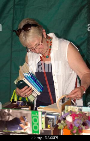 Woman browsing book stall at Worldham Village Fete, Hampshire, UK. Sunday 14 July 2013. - Stock Photo