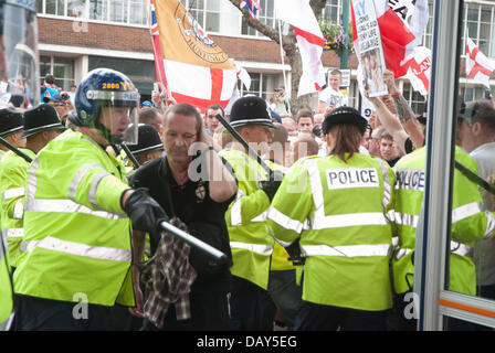 Birmingham, UK. 20th July, 2013. As blood flows from a head injury an English Defense League protester is escorted - Stock Photo