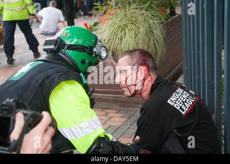 Birmingham, UK. 20th July, 2013. A police medic attends to an English Defence League protester as blood flows from - Stock Photo
