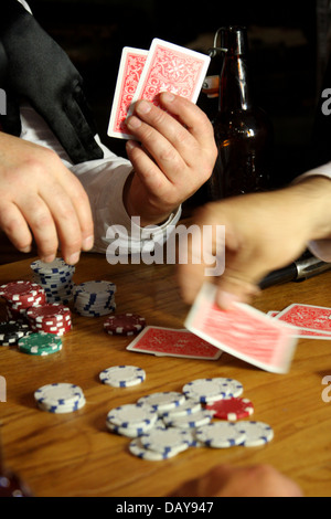 Men placing cards down on the table during an old west poker game - Stock Photo