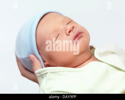 Closeup portrait of a cute newborn baby boy in mother's hands isolated on white background - Stock Photo