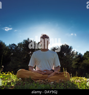 Chinese man meditating outdoors during sunrise in the nature, sitting with crossed legs on grass under blue sky - Stock Photo