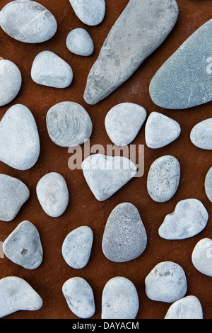 Pebble pattern on sandstone rock coloured by iron deposits from a underground water source - Stock Photo