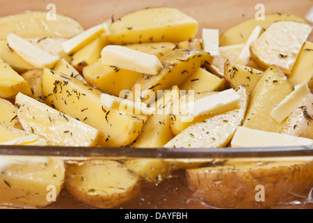 Raw potatoes in a glass tray marinated with olive oil, butter slices, thyme and salt, ready to be roasted - Stock Photo