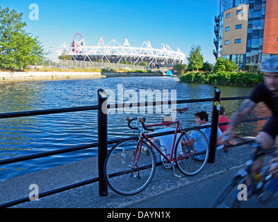 Male cycling along the River Lea (Lee) Navigation, Hackney Wick showing the Olympic Stadium and ArcelorMittal Orbit - Stock Photo