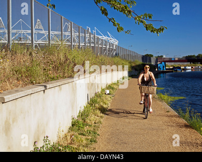 Female cyclist along the River Lea (Lee) Navigation in Hackney Wick showing the Olympic Stadium in Stratford - Stock Photo