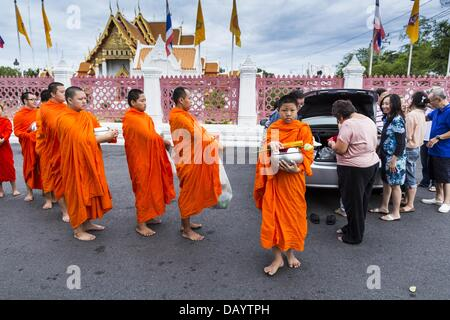 Bangkok, Thailand. 21st July, 2013. People present monks with alms and make merit at Wat Benchamabophit on the first - Stock Photo