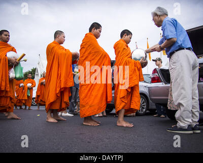 Bangkok, Thailand. 21st July, 2013. A man gives monks at Wat Benchamabophit food and alms on the first day of Vassa, - Stock Photo