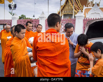 Bangkok, Thailand. 21st July, 2013. A family prays with Buddhist monks after making merit at Wat Benchamabophit - Stock Photo