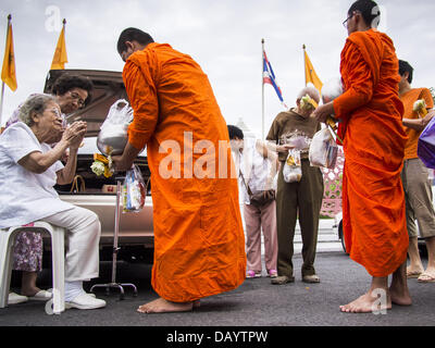 Bangkok, Thailand. 21st July, 2013. An elderly woman sits in a chair to give monks alms at Wat Benchamabophit on - Stock Photo