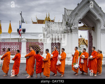 Bangkok, Thailand. 21st July, 2013. Buddhist monks at Wat Benchamabophit wait for people to present them with alms - Stock Photo
