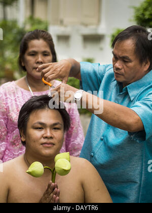 Bangkok, Thailand. 21st July, 2013. A young man's family cuts his hair before he became ordained as a Buddhist monk - Stock Photo